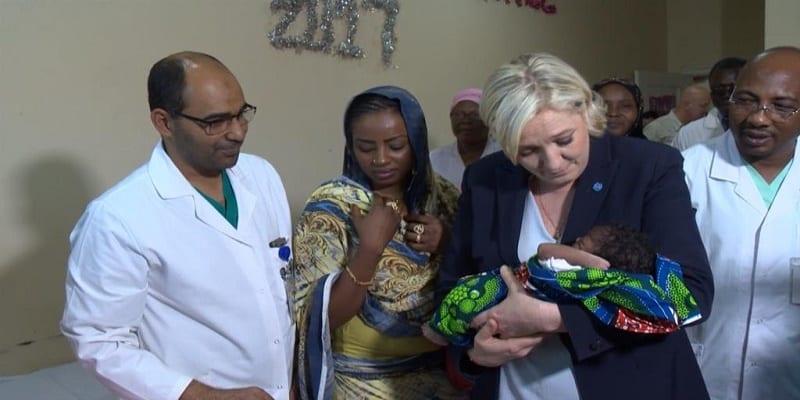 Photo de En visite au Tchad: Marine Le Pen prend un bébé noir dans ses bras. Réactions des Tchadiens